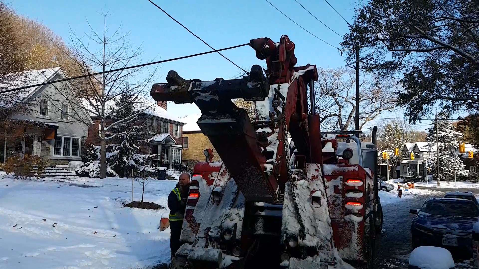 Alan lifts the wrecker to increase cable tension and pull the truck out of the snow