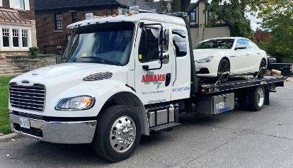 Abrams flatbed tow truck towing a sedan