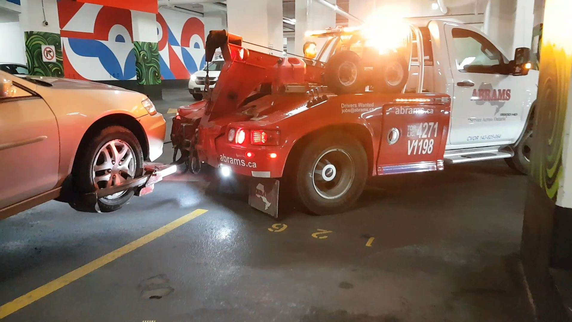 Tow truck driver pulls the car out of the parking spot