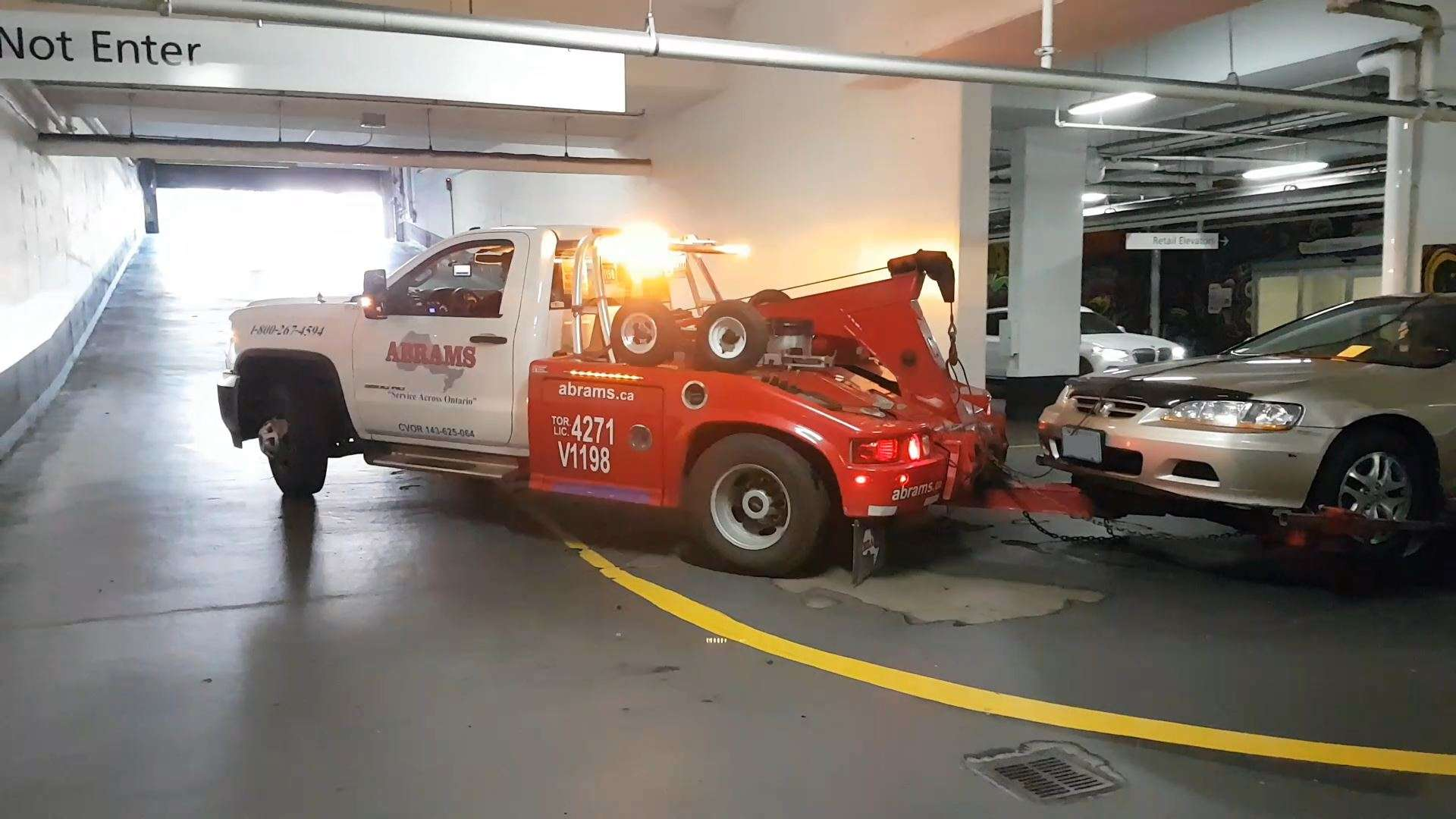 Tow truck driver pulls the car up the underground parking garage ramp
