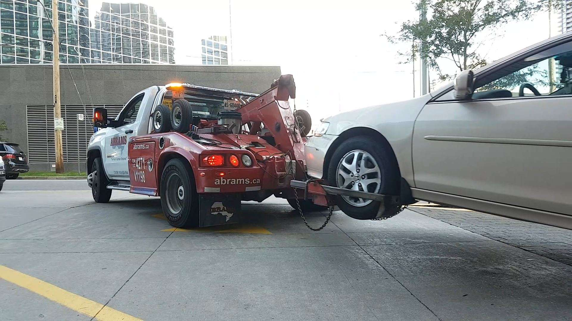 Tow truck driver pulls the car from the underground garage to the street