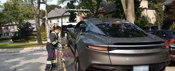 Tow truck operator tows an Aston Martin DBS on his flatbed